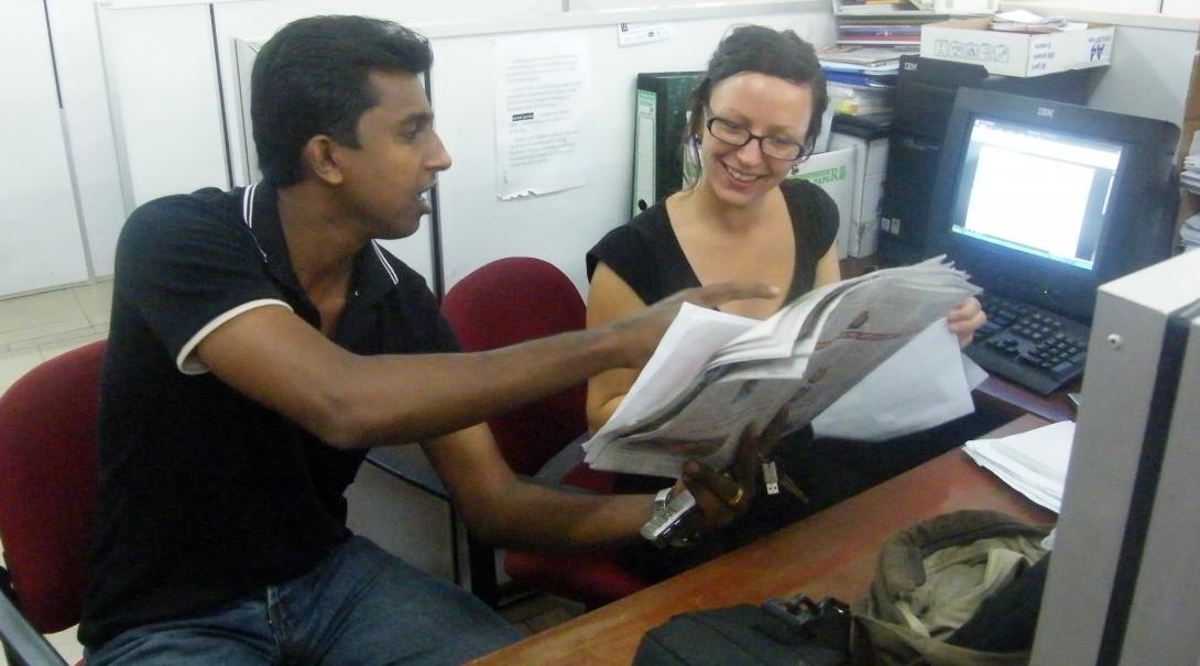 A Projects Abroad intern at her business placement in Sri Lanka checks the day's newspaper with local staff.